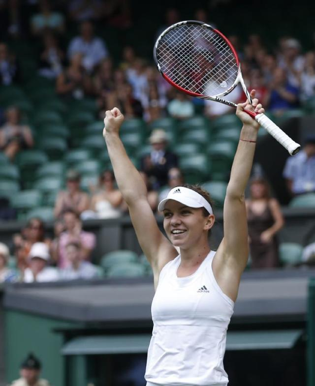 Simona Halep of Romania celebrates as she defeats Sabine Lisicki of Germany in their women's singles quarterfinal match at the All England Lawn Tennis Championships in Wimbledon, London, Wednesday, July 2, 2014. (AP Photo/Pavel Golovkin)