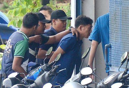 A North Korean man (R) identified by the Malaysian police as Ri Jong Chol and suspected by the authorities to be in connection with the murder of Kim Jong Nam, is taken to a police station in Sepang, Malaysia, February 18, 2017. Picture taken on February 18, 2017.  Park Jung-ho/News1 via REUTERS
