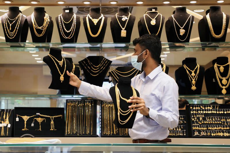 A vendor wearing a protective mask arranges gold jewellery displayed at VJ Gold and Diamond jewellery shop in Kuala Lumpur
