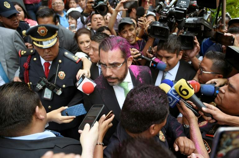Mexico City's security minister, Jesus Orta, is covered with glitter as he appealed for calm on August 12 (AFP Photo/ALFREDO ESTRELLA)