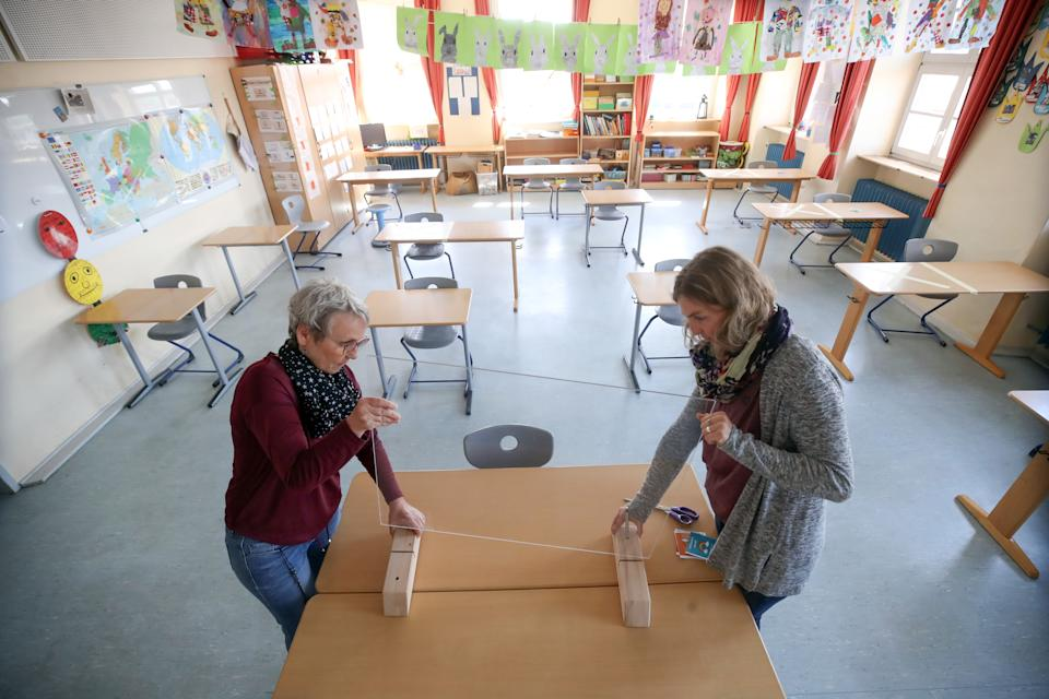HEPPENHEIM, GERMANY - APRIL 21: Staff install a Plexiglass pane on the teacher's table during preparations for reopening the temporarily-closed Schloss-Schule elementary school on April 21, 2020 in Heppenheim, Germany. Schools across Germany are making preparations to reopen in coming weeks as part of overall measures to ease the coronavirus lockdown. Certain precautions will accompany the resumption, including keeping pupils socially-distanced and the wearing of protective face masks. Germany is taking steps to lift elements of the lockdown in order to allow people to return to their jobs and for the economy to gain pace. (Photo by Alex Grimm/Getty Images)