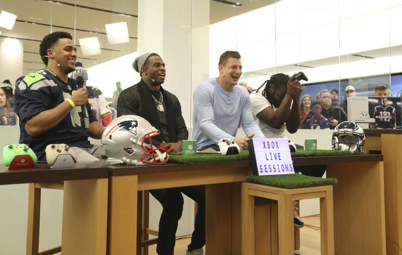 Host Rukari Austin, NFL Hall of Famer Deion Sanders, New England Patriots Rob Gronkowski, and Philadelphia Eagles LeGarrette Blount play some Xbox. (AP)