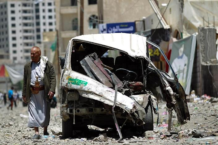 A Yemeni walks past a vehicle which was damaged the day before during an air strike by Saudi-led coalition warplanes on the nearby base on Fajj Attan hill on April 21, 2015 in the capital Sanaa (AFP Photo/Mohammed Huwais)