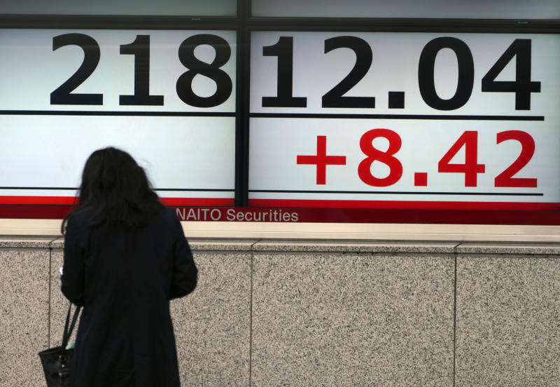 A woman looks at an electronic stock board showing Japan's Nikkei 225 index at a securities firm in Tokyo Friday, Nov. 16, 2018. Shares were mixed in early trading in Asia on Friday on revived concerns over the prospects for a breakthrough in trade tensions between the U.S. and China.(AP Photo/Eugene Hoshiko)