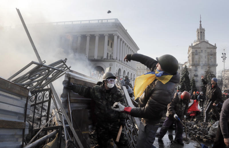 An anti-government protester throws a stone during clashes with riot police in Kiev's Independence Square, the epicenter of the country's current unrest, Kiev, Ukraine, Wednesday, Feb. 19, 2014. The deadly clashes in Ukraine's capital have drawn sharp reactions from Washington, generated talk of possible European Union sanctions and led to a Kremlin statement blaming Europe and the West. (AP Photo/Efrem Lukatsky)