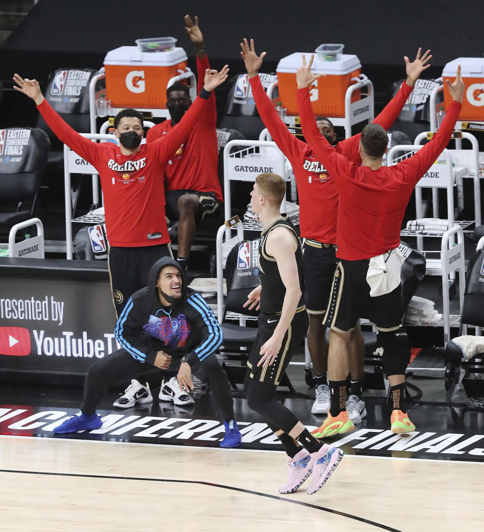 Injured Atlanta Hawks guard Trae Young and the bench react as Kevin Huerter hits a 3-pointer against the Milwaukee Bucks during the fourth quarter in Game 4 of the Eastern Conference finals in the NBA basketball playoffs Tuesday, June 29, 2021, in Atlanta. (Curtis Compton/Atlanta Journal-Constitution via AP)