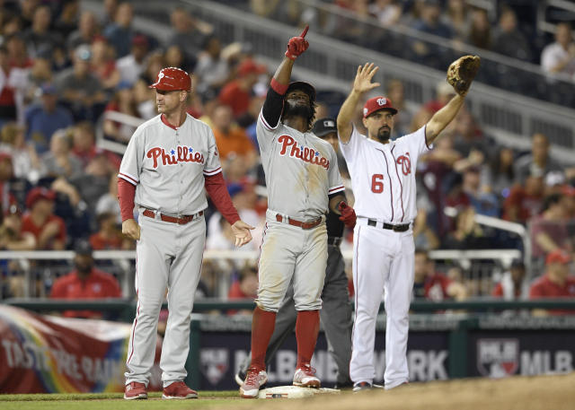 Philadelphia Phillies' Odubel Herrera, center, points as he stands on third with a triple that drove in two runs during the fifth inning of a baseball game next to Washington Nationals third baseman Anthony Rendon (6), Sunday, June 24, 2018, in Washington. Phillies third base coach Dusty Wathan stands at left. (AP Photo/Nick Wass)