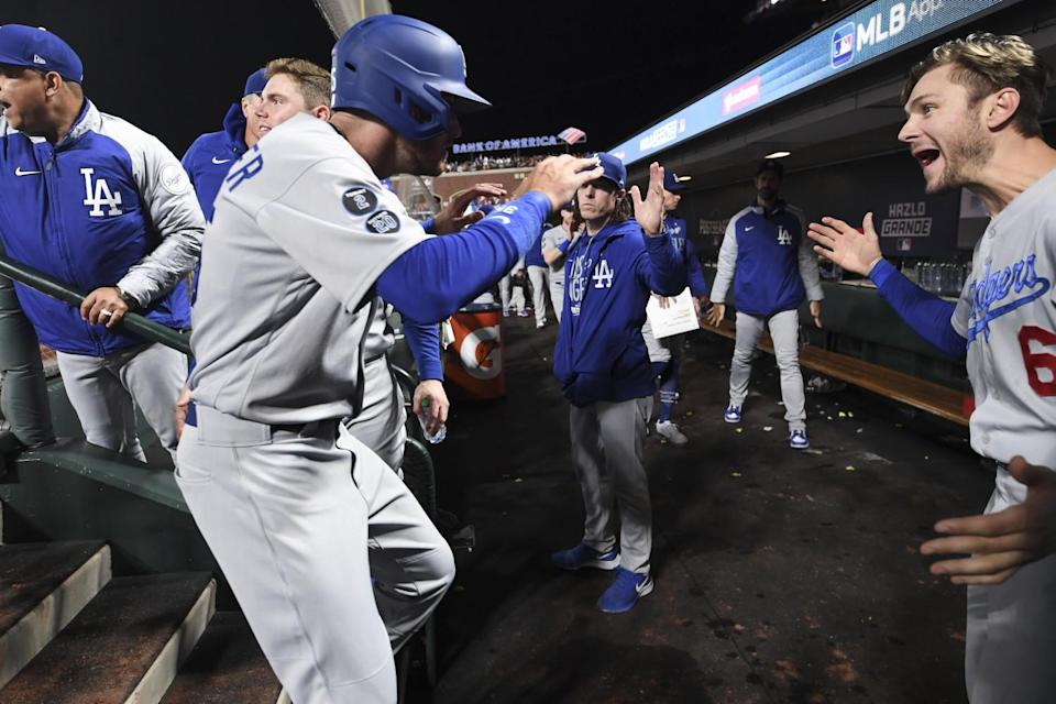 Cody Bellinger celebrates with Dodgers teammate Trea Turner in the dugout.