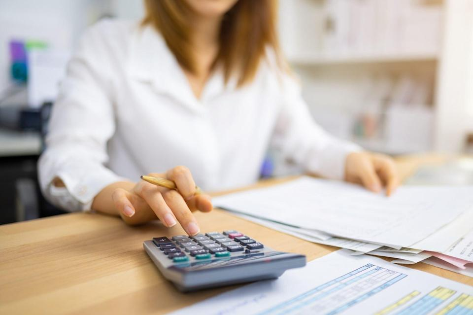 An image of a woman wit a calculator.