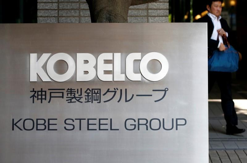 FILE PHOTO: A man walks past the signboard of Kobe Steel at the group's Tokyo headquarters in Tokyo