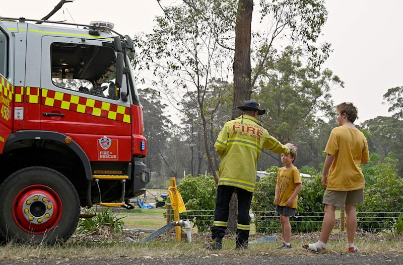 A firefighter talks to residents in Old Bar, NSW.