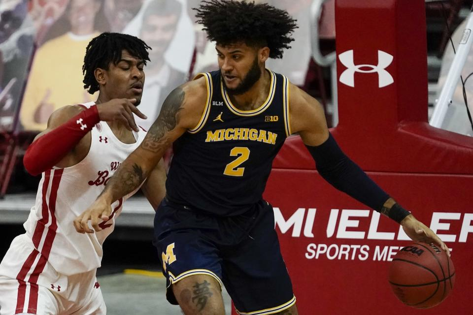 Wisconsin's Aleem Ford defends Michigan's Isaiah Livers during the first half of an NCAA college basketball game Sunday, Feb. 14, 2021, in Madison, Wis. (AP Photo/Morry Gash)