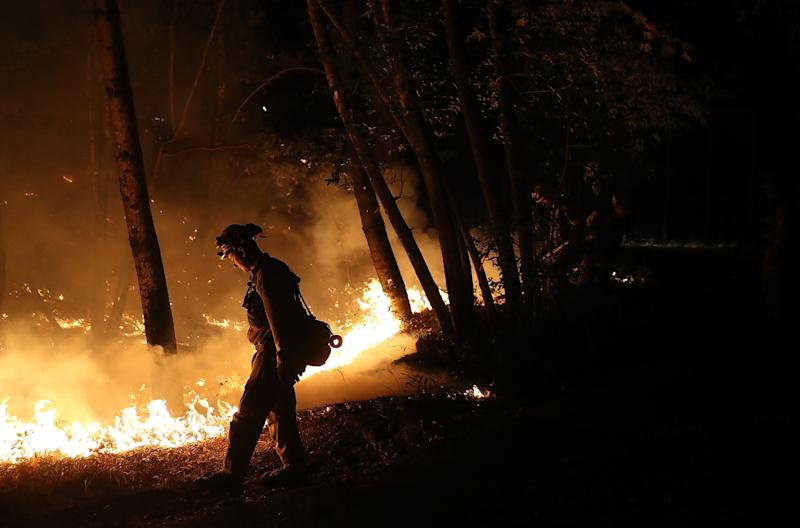 Cal Fire firefighter Brandon Tolp uses a drip torch during a firing operation while battling the Tubbs Fire on Oct. 12, 2017, near Calistoga, California.