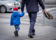 A man and his son walk in downtown Frankfurt, Germany, Tuesday, Jan. 19, 2021. German politics decides about further Coronavirus restrictions on Tuesday. (AP Photo/Michael Probst)