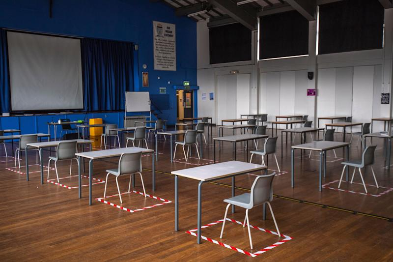 Socially distanced desks are set out for lesson in the hall at a school in Dukinfield, England. (Anthony Devlin via Getty Images)