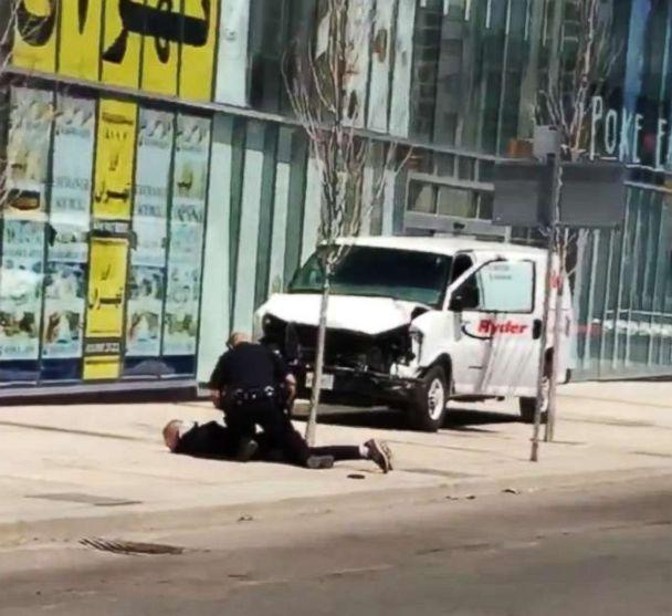 PHOTO: Video footage shows a police officer confronting the man who allegedly rammed into pedestrians with a van in Toronto, Canada, April 23, 2018. (Handout via Storyful)