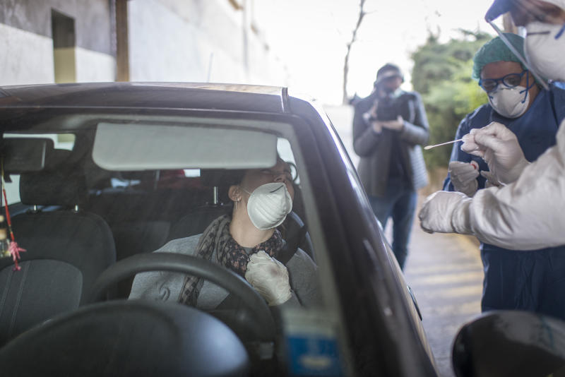 Healthcare workers perform a swab test on woman in her car. Source: AAP