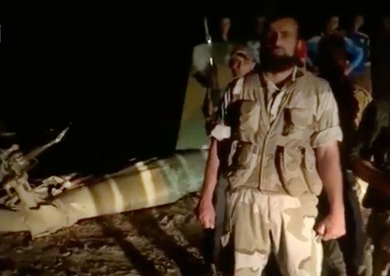 In this Sunday, May 5, 2013 image taken from video obtained from the Shaam News Network, which has been authenticated based on its contents and other AP reporting, armed men stand near the wreckage of a military helicopter, left, in Deir el-Zour, Syria. Syrian rebels shot down a military helicopter in the country's east, killing eight government troops on board a day after opposition forces entered a sprawling military air base in the north, activists said Monday. (AP Photo/Shaam News Network via AP video)