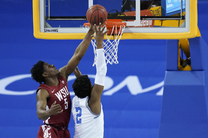Washington State guard T.J. Bamba (5) deflects a shot by UCLA forward Cody Riley (2) during the first half of an NCAA college basketball game Thursday, Jan. 14, 2021, in Los Angeles. (AP Photo/Ashley Landis)