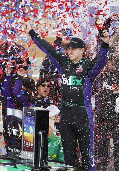 Denny Hamlin celebrates in victory lane after winning the NASCAR Sprint Cup Series auto race at Kansas Speedway in Kansas City, Kan., Sunday, April 22, 2012. (AP Photo/Orlin Wagner)