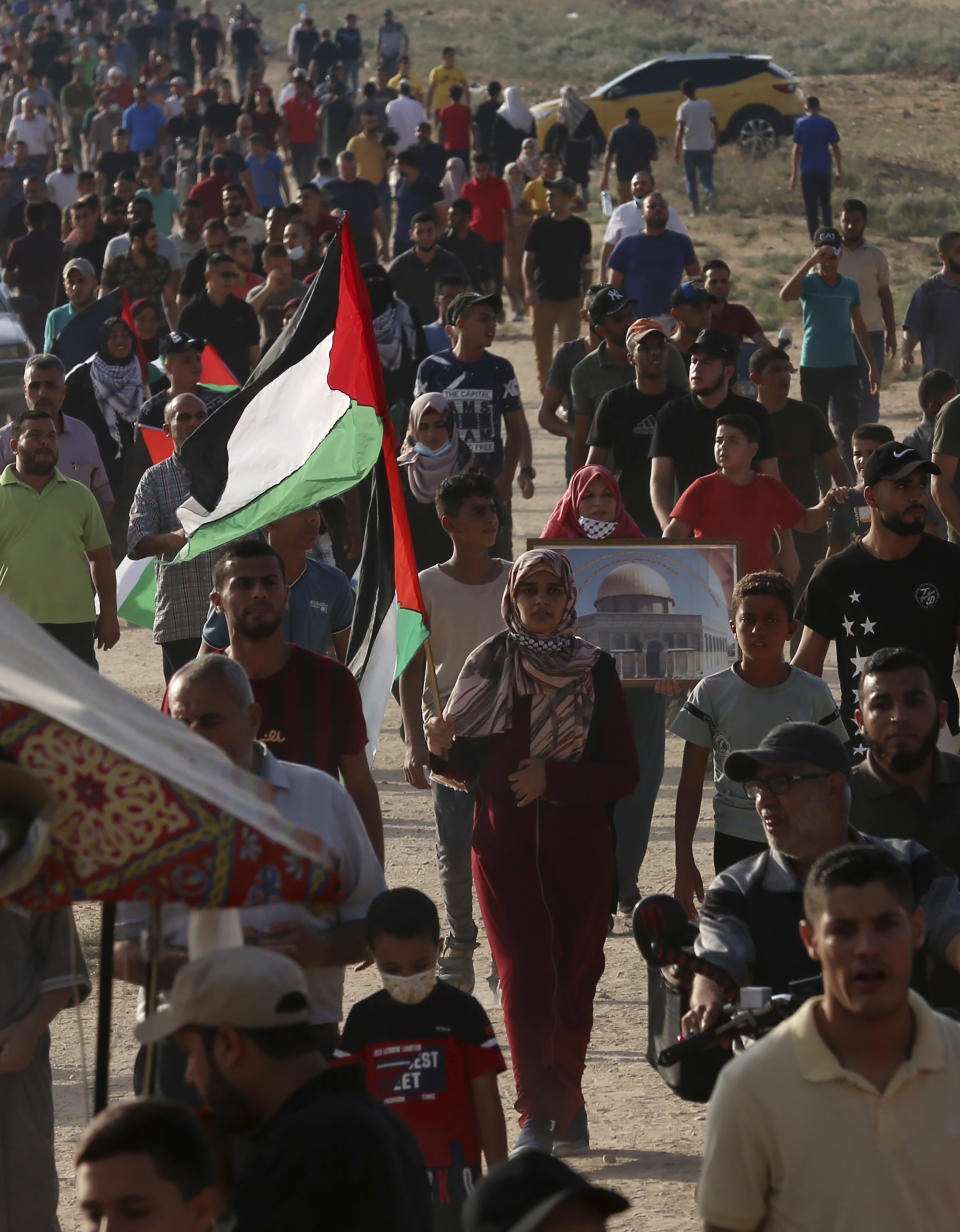 Protestors march toward the Gaza Strip's border with Israel, during a protest marking the anniversary of a 1969 arson attack at Jerusalem's Al-Aqsa mosque by an Australian tourist later found to be mentally ill, east of Gaza City, Saturday, Aug. 21, 2021. (AP Photo/Adel Hana)