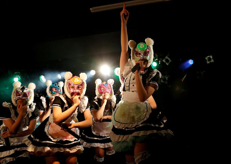 Members of Japan's idol group 'Virtual Currency Girls' wearing cryptocurrency-themed masks perform in their debut stage event in Tokyo, Japan. Photo: Kim Kyung-Hoon/Reuters