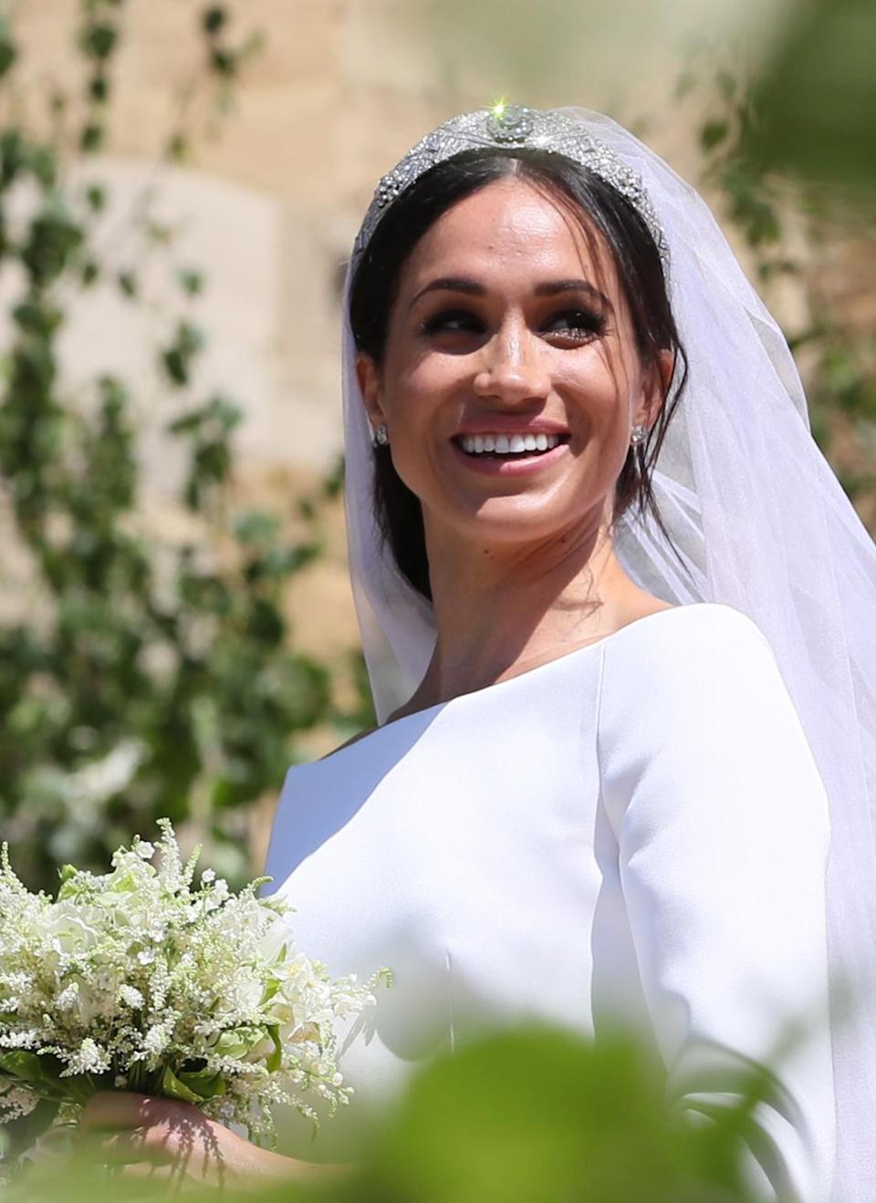 <p>She may have married into the royal family on May 19 but the former actress still injected her own personal style into the big day. Accessorised with Queen Mary's Filigree tiara and a Givenchy veil, the Duchess of Sussex wore a wispy low bun to wed Prince Harry. <em>[Photo: Getty]</em> </p>