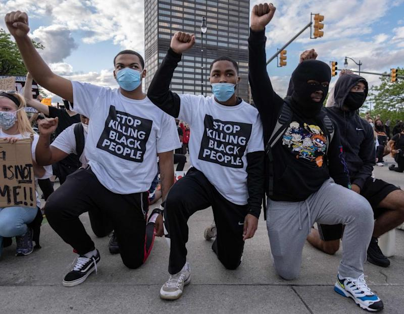 Protesters raise their fists as they kneel in front of a police station in Detroit, Michigan, on 30 May.