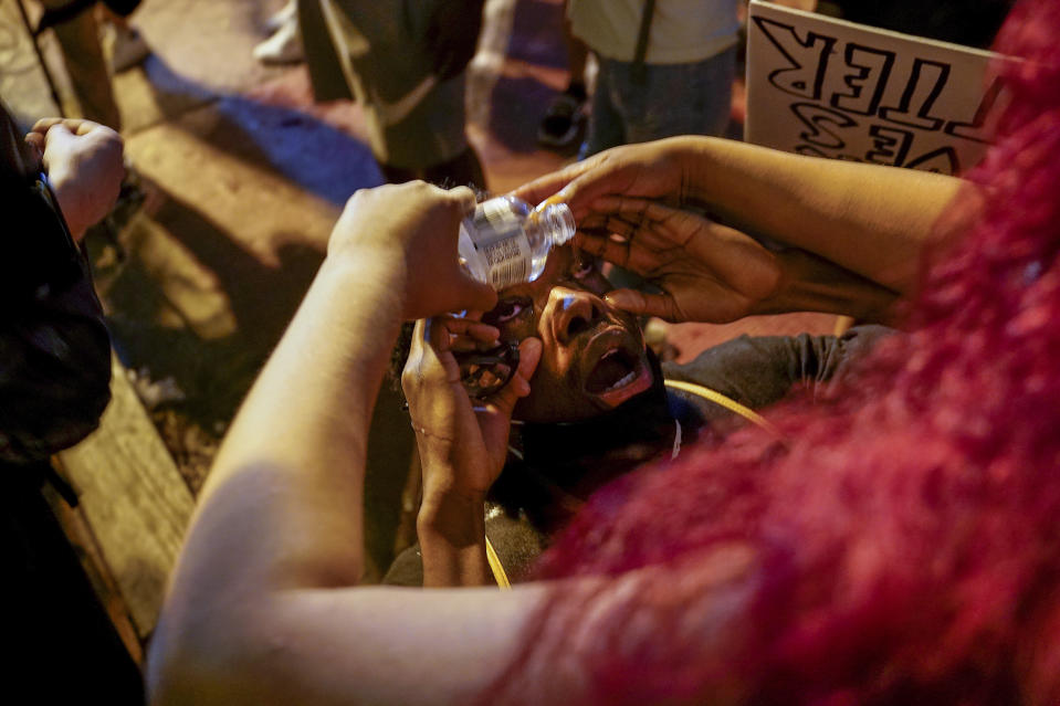 A demonstrator has their eyes flushed as people protest the death of George Floyd, Saturday, May 30, 2020, near the White House in Washington. (AP Photo/Evan Vucci)
