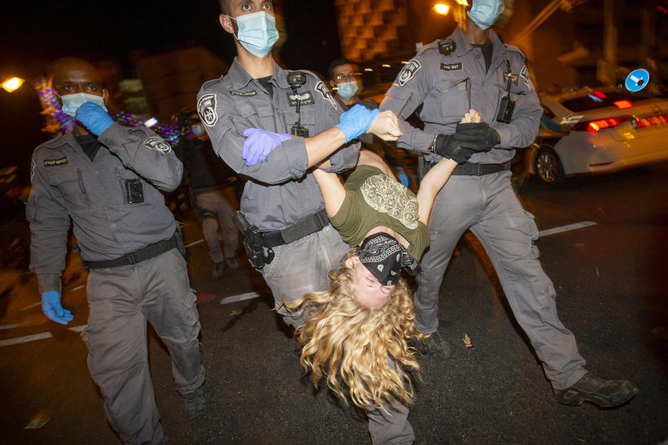 Israeli Police officers drag a protester as they forcibly clear the square outside Israeli Prime Minister Benjamin Netanyahu's residence in Jerusalem, early Sunday, Oct. 18, 2020. (AP Photo/Ariel Schalit)