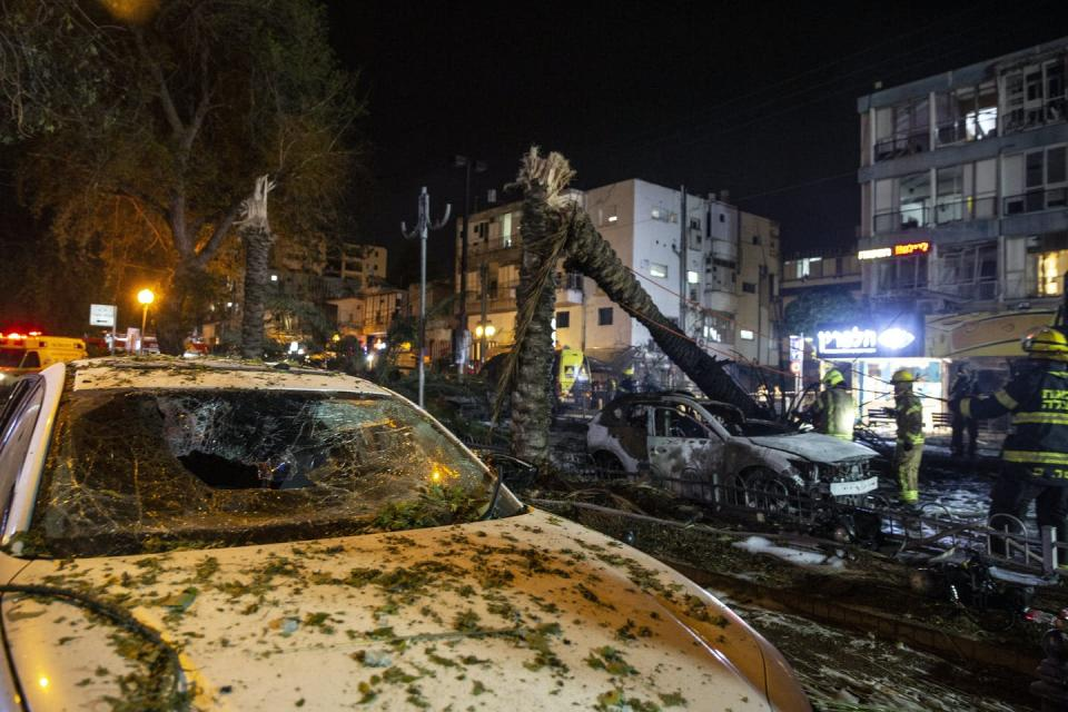 Rocket destruction, including decimated palm trees and cars covered in rubble and debris.