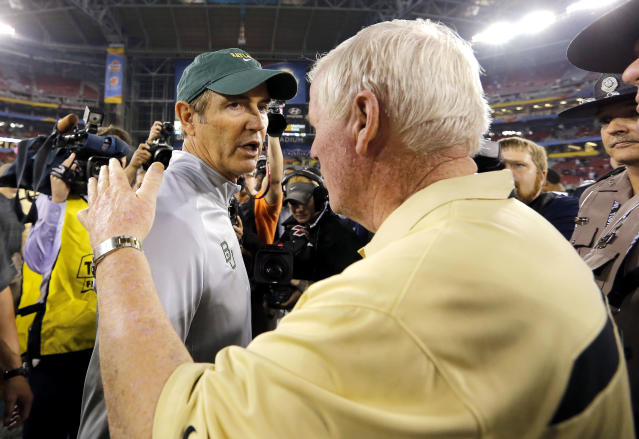 Central Florida head coach George O'Leary, right, greets Baylor head coach Art Briles at mid-field after the Fiesta Bowl NCAA college football game against Baylor, Wednesday, Jan. 1, 2014, in Glendale, Ariz. Central Florida won 52-42. (AP Photo/Matt York)