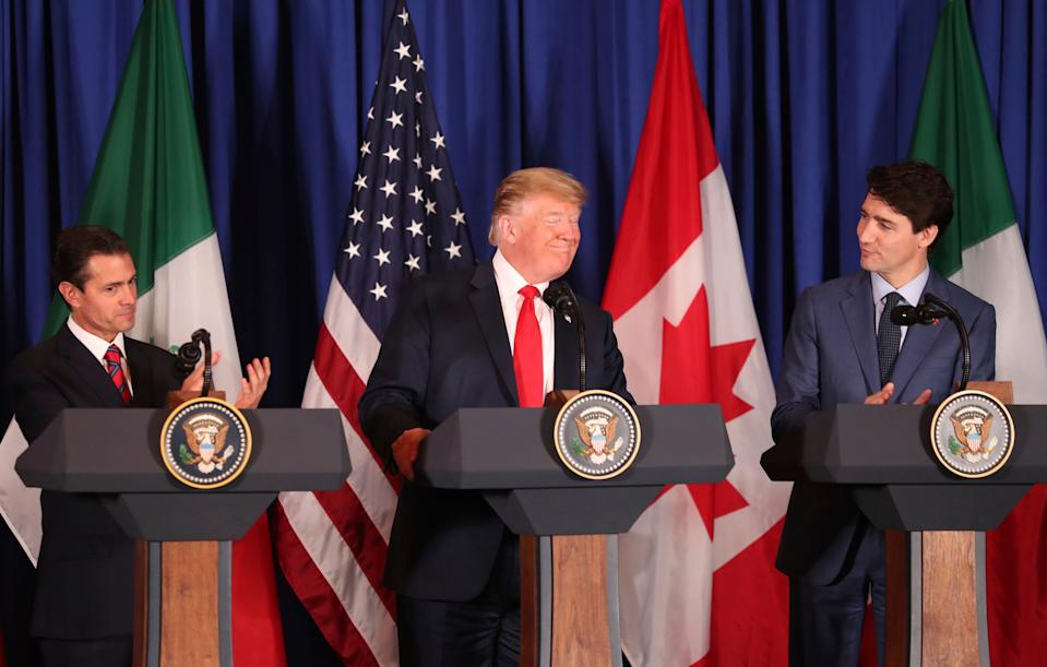 Flanked by Mexico's President Enrique Pena Nieto, left, and Canada's Prime Minister Justin Trudeau, President Donald Trump smiles during a signing ceremony of their trilateral trade agreement, on the sidelines of the Group of 20 summit in Buenos Aires, Argentina, on Friday, Nov. 30, 2018. The United States-Mexico-Canada Agreement, or USMCA as Trump refers to it, must still be approved by lawmakers in all three countries. (AP Photo/Martin Mejia)