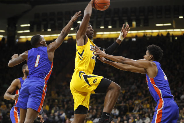 Iowa forward Tyler Cook, center, drives to the basket over Savannah State's Zaquavian Smith, left, and Romani Hansen, right, during the first half of an NCAA college basketball game, Saturday, Dec. 22, 2018, in Iowa City, Iowa.(AP Photo/Charlie Neibergall)