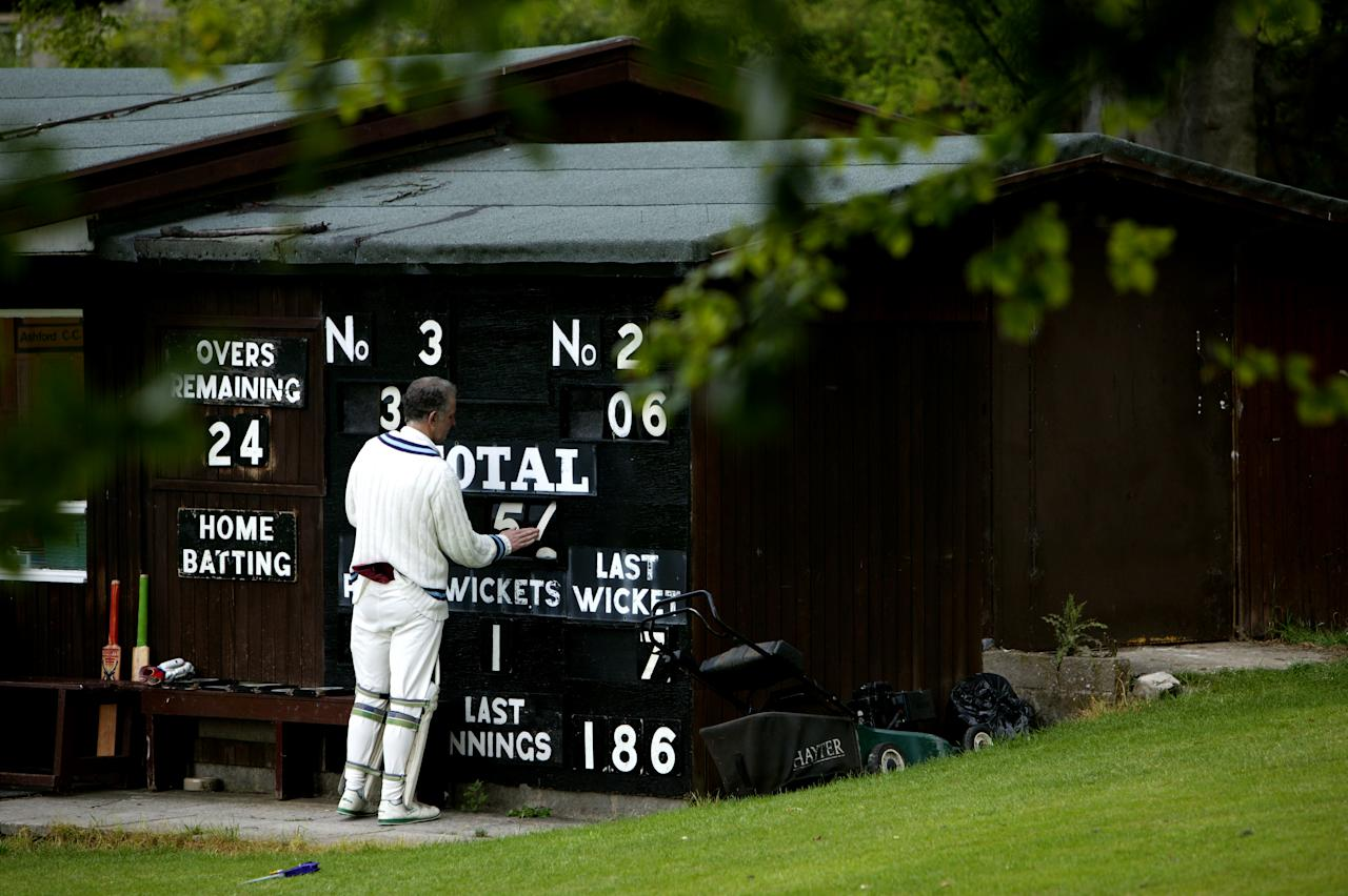 ASHFORD IN THE WATER, ENGLAND - JUNE 12: A Cricketer from Ashford in the Water Cricket Club adjusts the score board during a match on June 12, 2005 in Ashford in the Water, England.  (Photo by Laurence Griffiths/Getty Images)