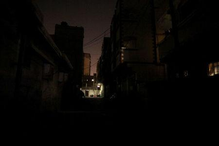 Palestinians sit outside their houses as they escpae from the heat during power cut in Shati refugee camp in Gaza City July 2, 2017. The houses are lit by battery-powered LED light bulbs. REUTERS/Mohammed Salem
