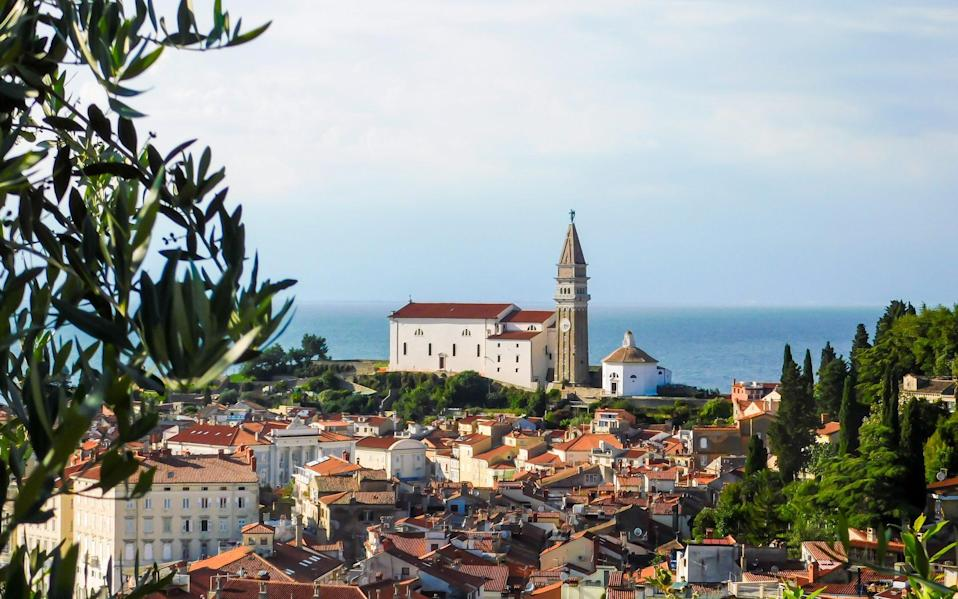 rooftops overlooking sea with church in prominent view - Getty Images/EyeEm