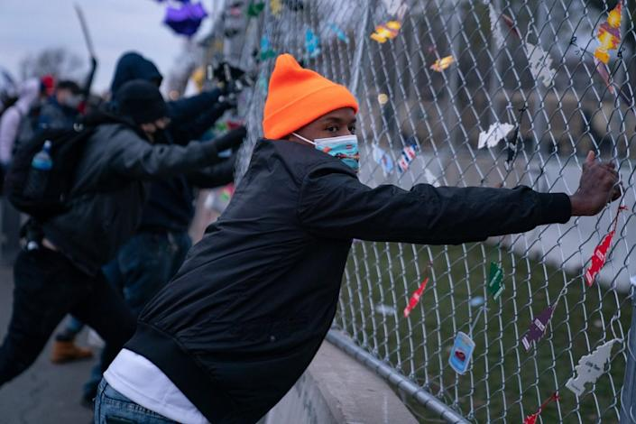 Protesters pull on a fence.