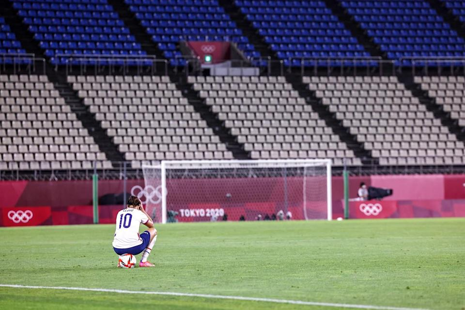 USA's Carli Lloyd sits alone on the field in long after losing a semifinal match against Canada