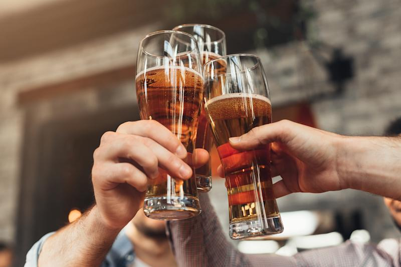 Friends toasting with glasses of beer, resting at the pub, closeup