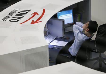 An employee of the Tokyo Stock Exchange stretches at the bourse in Tokyo