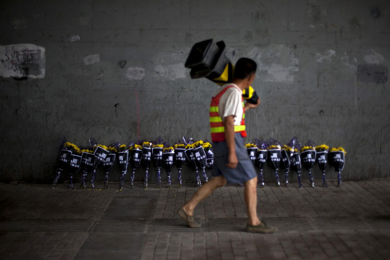 """A roadworker walks past flowers placed under a bridge where a man drowned on Saturday, July 21 in his flooded car on a main road in Beijing Friday, July 27, 2012. Chinese characters on the wraps read """"One Rain, One Day of Mourning."""" The storm that ravaged Beijing nearly a week ago and killed at least 77 people remains a sensitive topic in China, with a newspaper ordered to cut its coverage and online discussions curtailed. (AP Photo/Alexander F. Yuan)"""