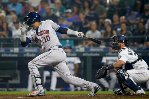 Houston Astros' Yuli Gurriel follows through on an RBI single that scored Carlos Correa during the sixth inning of a baseball game against the Seattle Mariners Tuesday, Aug. 21, 2018, in Seattle. (AP Photo/Jennifer Buchanan)