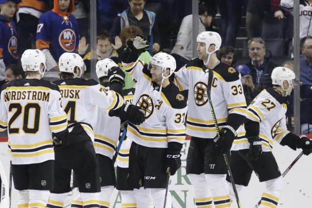 Boston Bruins' Patrice Bergeron (37) celebrates with teammates after scoring the winning goal during the overtime period of an NHL hockey game against the New York Islanders, Saturday, Jan. 11, 2020, in New York. (AP Photo/Frank Franklin II)