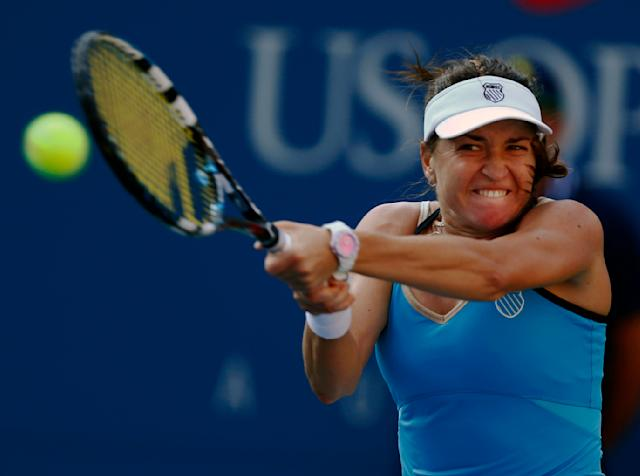 Alexandra Dulgheru, of Romania, follows through on a shot against Maria Sharapova, of Russia, during the second round of the 2014 U.S. Open tennis tournament, Wednesday, Aug. 27, 2014, in New York. (AP Photo/Matt Rourke)