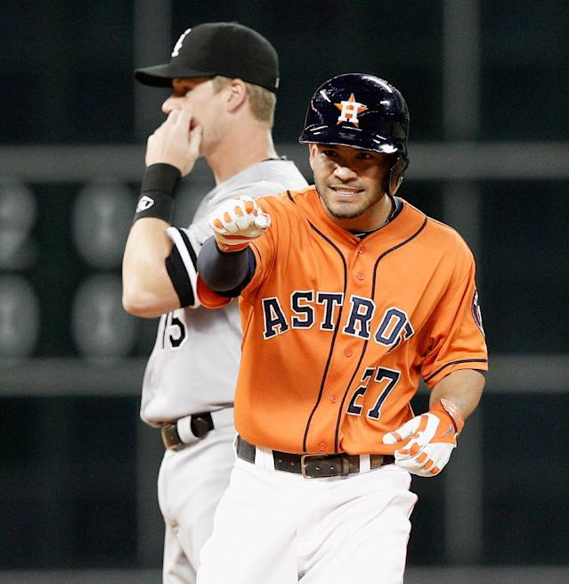 Houston Astros' Jose Altuve (27) motions to the dugout after reaching second base in the fifth inning as Chicago White Sox second baseman Gordon Beckham (15) looks on during a baseball game on Friday, May 16, 2014, in Houston. (AP Photo/Bob Levey)
