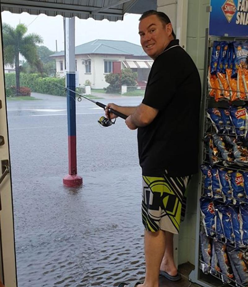A man stands out the door of Valley Cash Store with a fishing rod as rain brings floods.