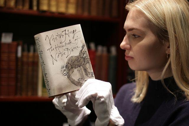An employee holds a first edition copy of 'The Hunchback of Notre-Dame' by Victor Hugo with a dust-jacket designed by Quentin Blake