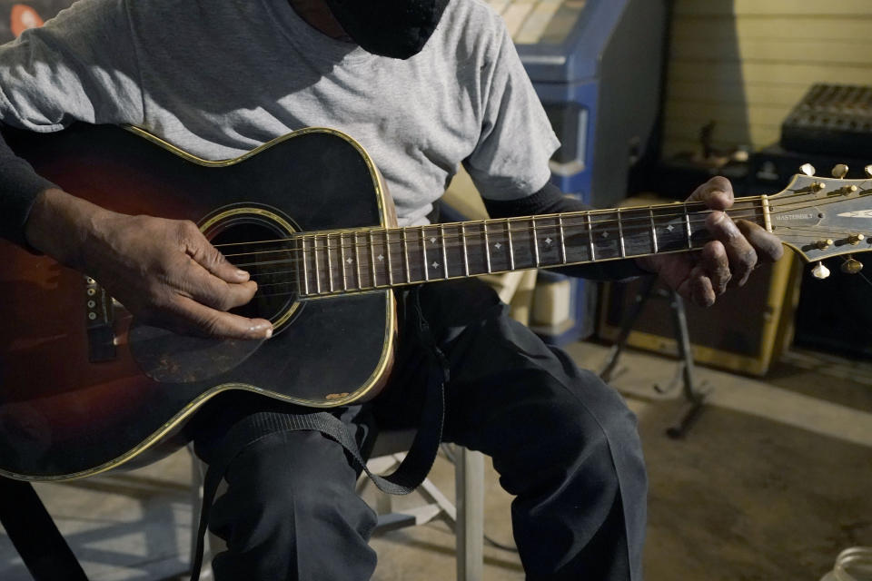 "Blues performer Jimmy ""Duck"" Holmes plays a quick ditty at the Blue Front Cafe in Bentonia, Miss., Jan. 21, 2021. Holmes' ninth album, ""Cypress Grove,"" has earned a Grammy nomination for the Best Traditional Blues Album. (AP Photo/Rogelio V. Solis)"