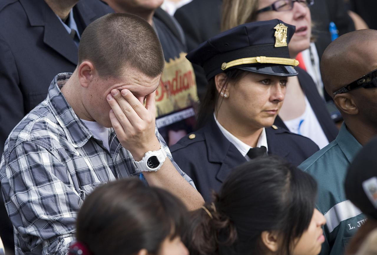 NEW YORK, NY - SEPTEMBER 11:  People observe a moment of silence at the time the second hijacked airliner crashed into the south tower of the World Trade Center  during the tenth anniversary ceremonies of the September 11, 2001 terrorist attacks at the World Trade Center site, September 11, 2011 in New York City. New York City and the nation are commemorating the tenth anniversary of the terrorist attacks which resulted in the deaths of nearly 3,000 people after two hijacked planes crashed into the World Trade Center, one into the Pentagon in Arlington, Virginia and one crash landed in Shanksville, Pennsylvania.  (Photo by Kristoffer Tripplaar-Pool/Getty Images)